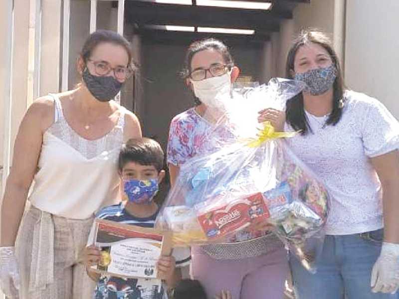 A diretora e vice-diretora, Regina Benassi e Josiane Suave, entregam prêmio ao aluno Vinícius Lima