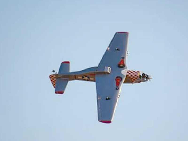Um Avião Aeromodelo sobrevoando em cima da pista de pouso e decolagens