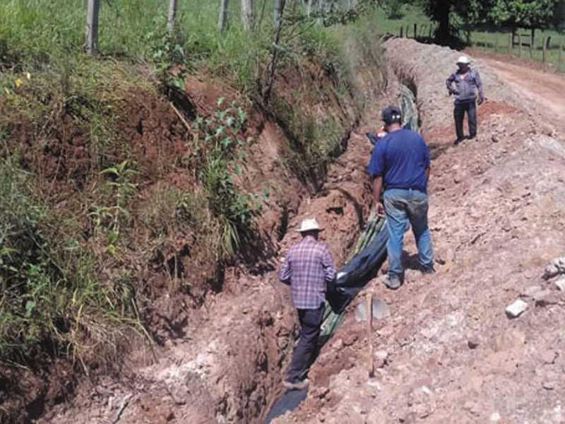 Os funcionário da prefeitura trabalhando na  estrada de acesso ao bairro Pinheirinho