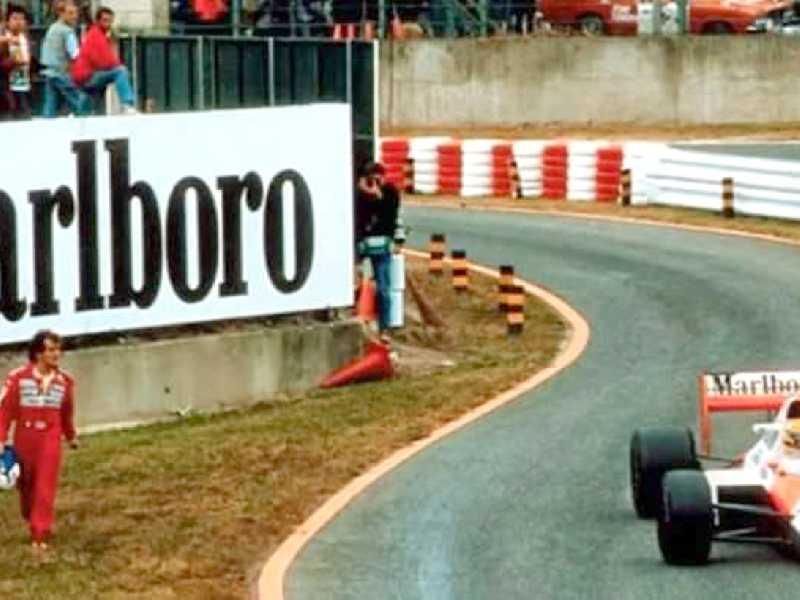 Prost (E) caminha para a torre de cronometragem, enquanto Senna entra nos box, vence, e é desclassificado