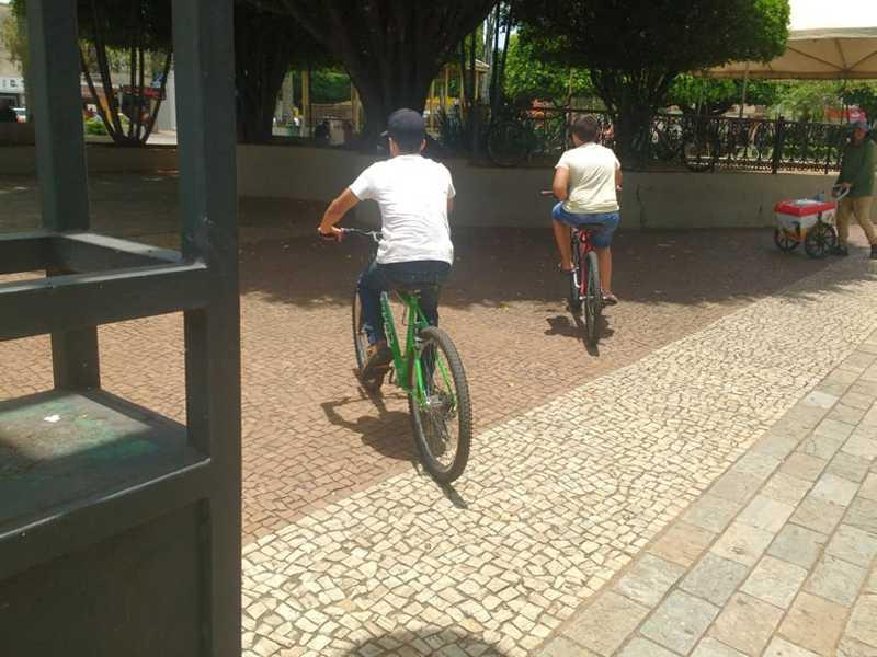 Ciclistas transitando irregularmente e livremente pelo calçadão e Praça Com. José Honório, bem no centro de Paraíso