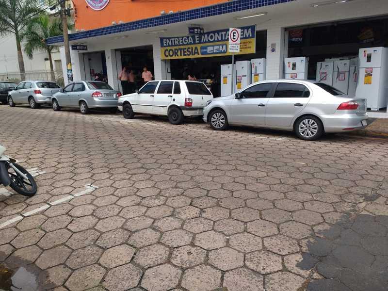 Veículos estacionados irregularmente em horário comercial em vaga exclusiva para cargas e descargas