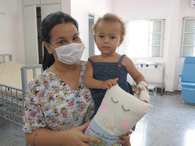 Enfermeira Gisele dos Reis Silva com criança paciente na pediatria