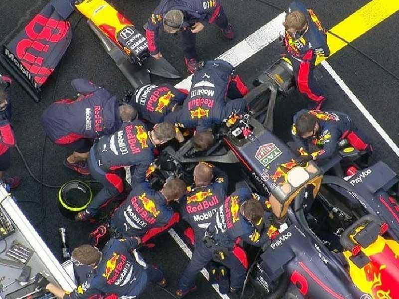 Mecânicos da Red Bull debruçados no carro  de Verstappen para colocá-lo na corrida