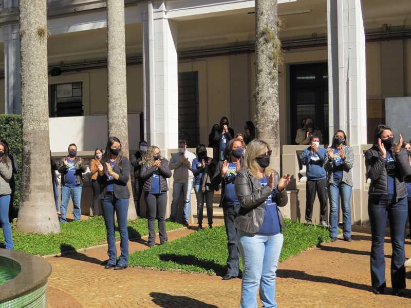 Colaboradores realizam salva de palmas para comemorar os 50 anos da instituição